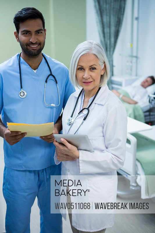 Portrait of smiling surgeon and doctor while consulting patient in ward