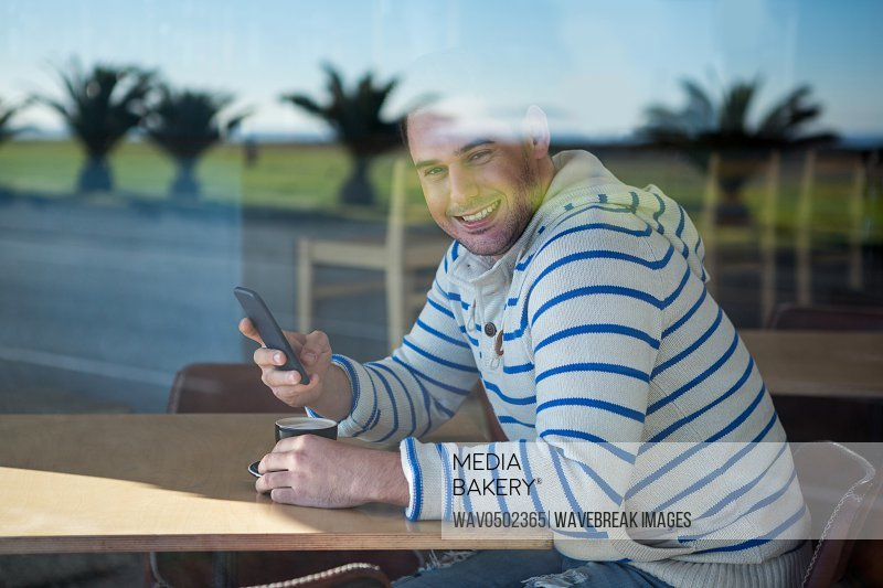 Portrait of smiling man using mobile phone in the coffee shop