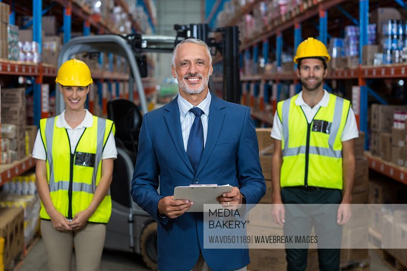 Portrait of warehouse manager and co-workers standing with clipboard in warehouse