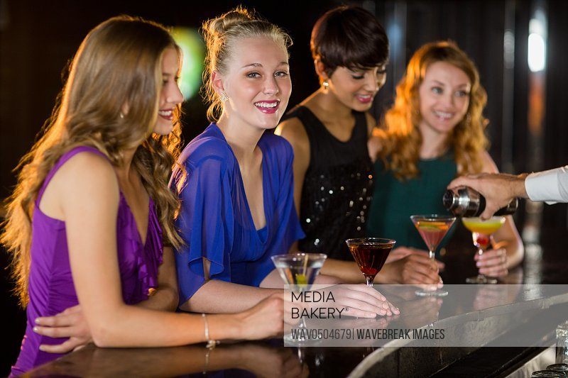Smiling woman with cocktail standing at bar counter with her friends