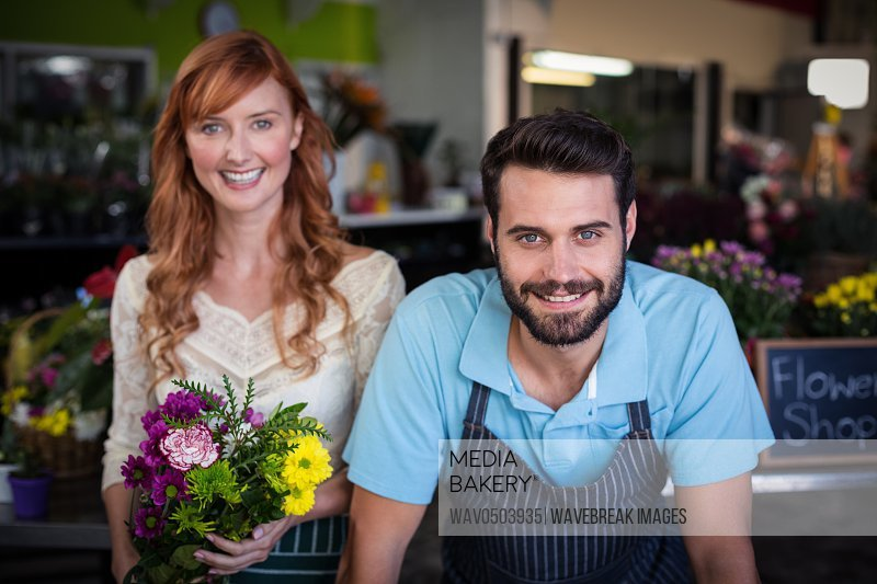 Portrait of couple standing and smiling in the flower shop