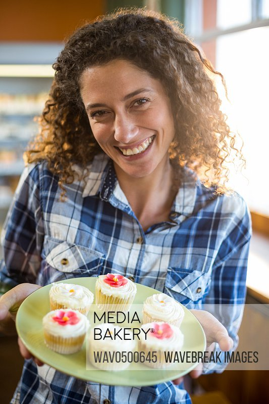 Portrait of smiling woman holding plate of cup cake in supermarket