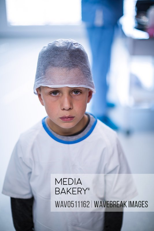 Portrait of upset boy in surgical cap at hospital
