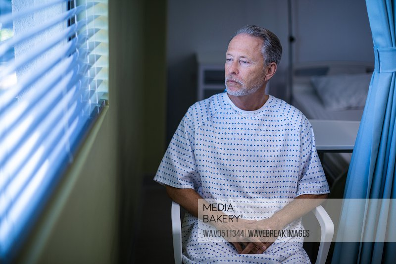Sick patient sitting on chair and looking through window blinds in hospital