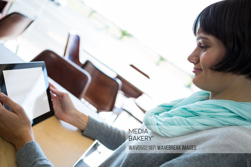 Smiling woman using digital tablet in cafeteria