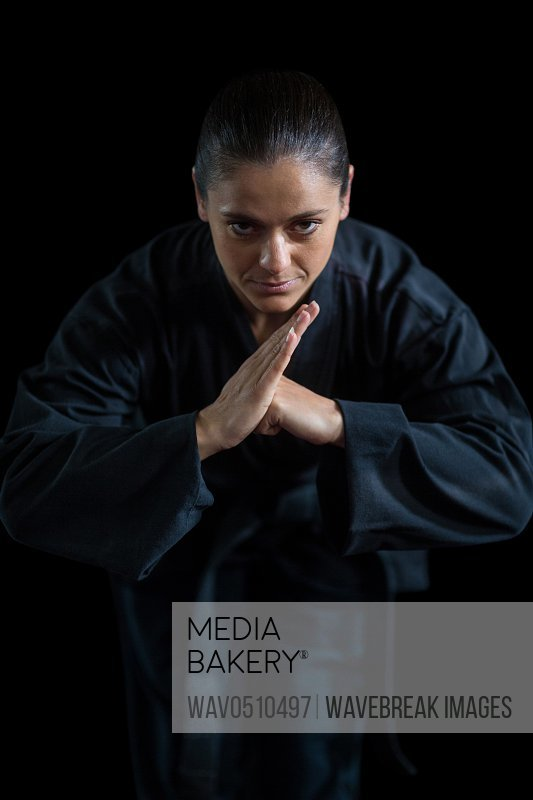 Female karate player performing karate stance against black background