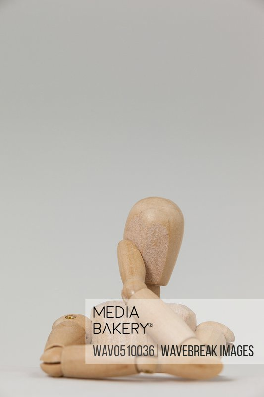 Wooden figurine leaning on table against white background