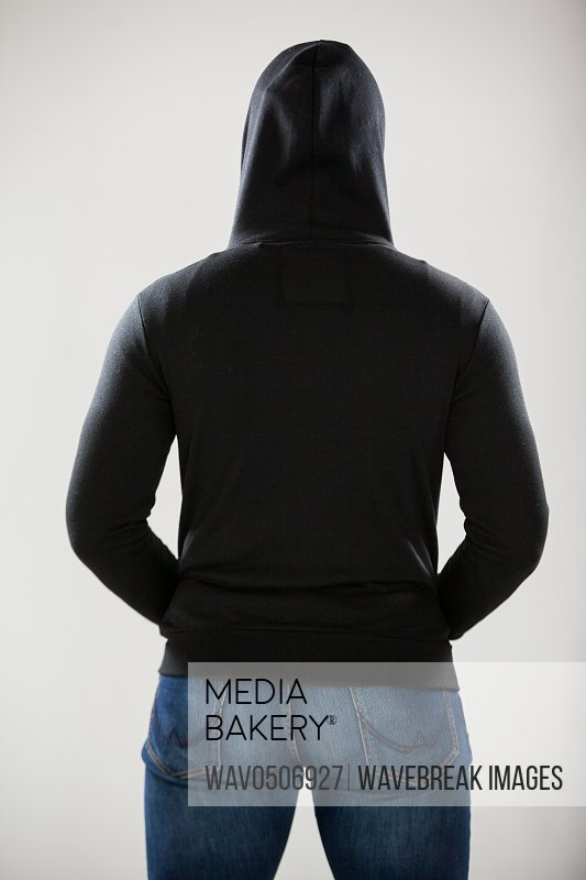 Rear view of spy in a hoodie standing against white background
