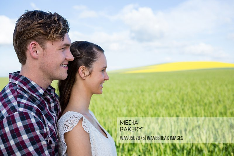 Romantic couple standing in field on a sunny day