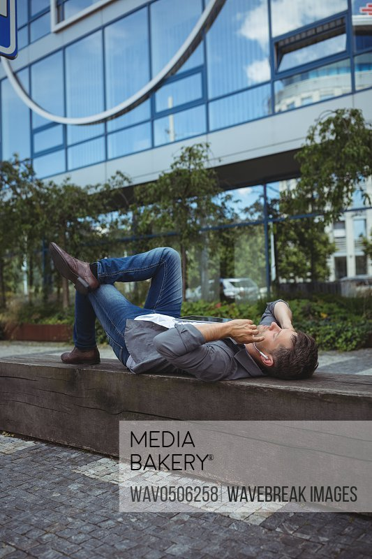 Business executive lying on wood and listening music outside office