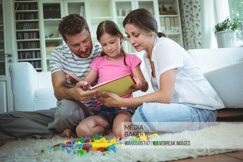 Parents and daughter reading a book while playing with building blocks at home