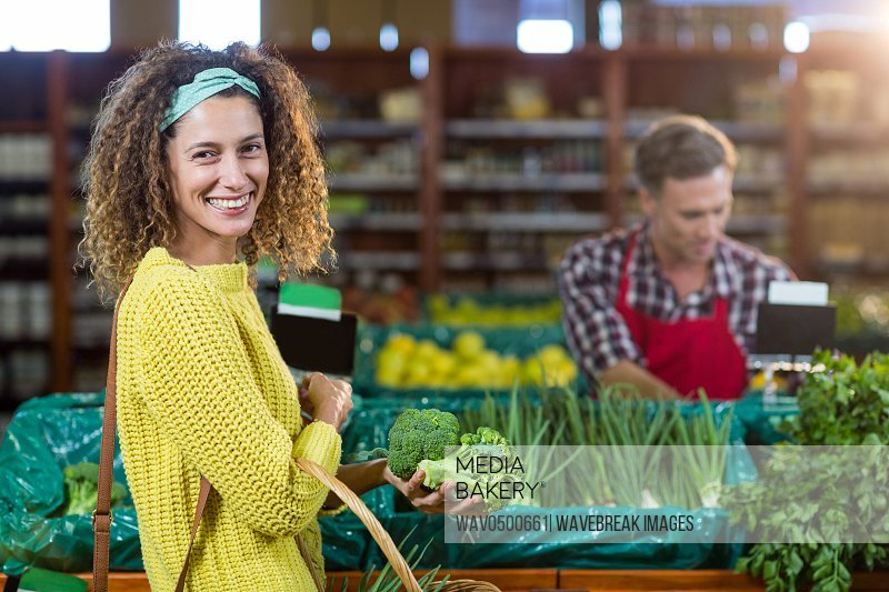 Portrait of smiling woman buying vegetables in organic section of supermarket
