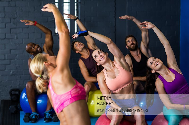 Male and female athletes smiling while exercising with instructor in fitness studio