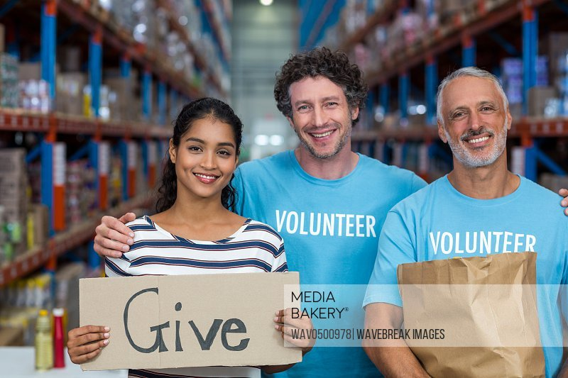 Happy colleagues holding sign boards with give message in warehouse