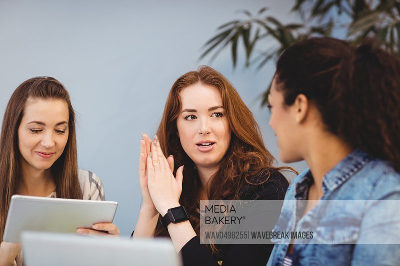 Creative businesswomen discussing at desk while using digital tablet in office