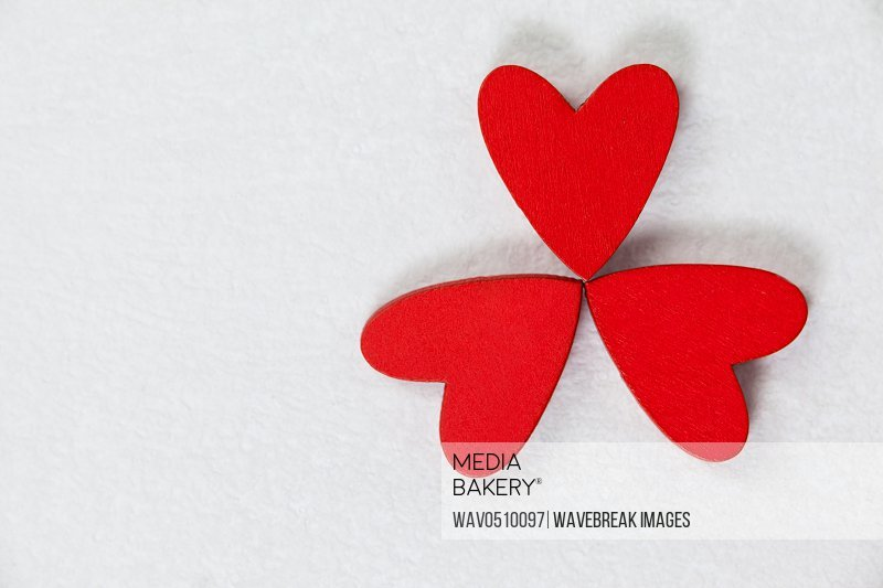 Three red hearts forming a clover leaf against white background