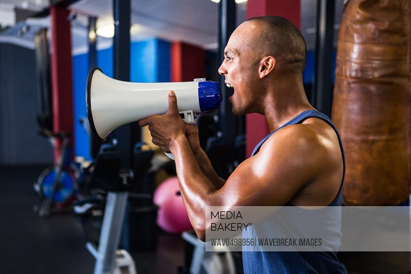 Side view of male athlete shouting through megaphone in fitness studio