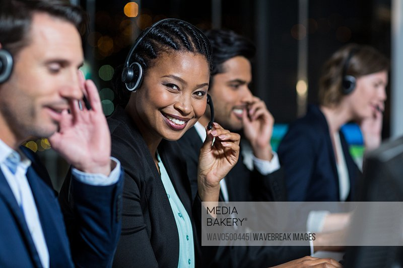 Portrait of businesswoman with headsets using computer at office desk