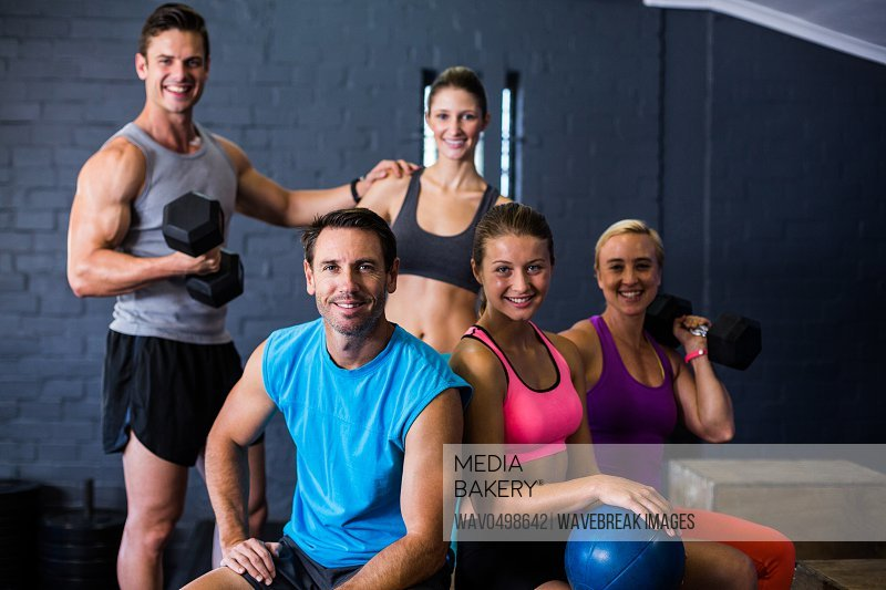 Portrait of happy male and female athletes in fitness studio