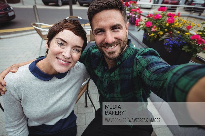Portrait of couple posing for selfie in cafeteria
