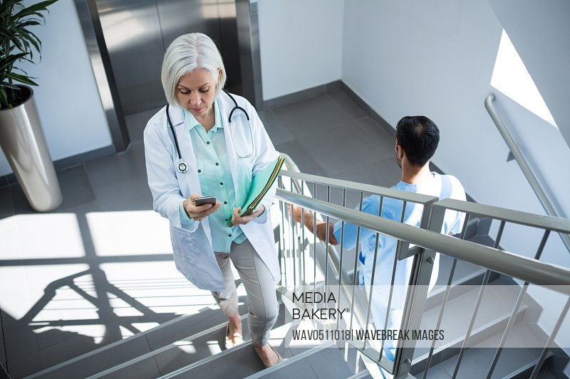 Doctor using mobile phone while walking on staircase in hospital
