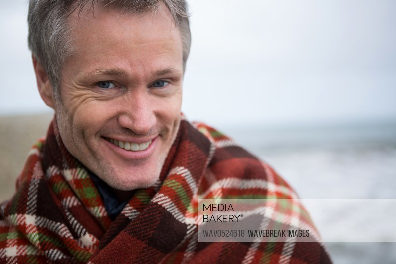 Smiling man wrapped in shawl at the beach