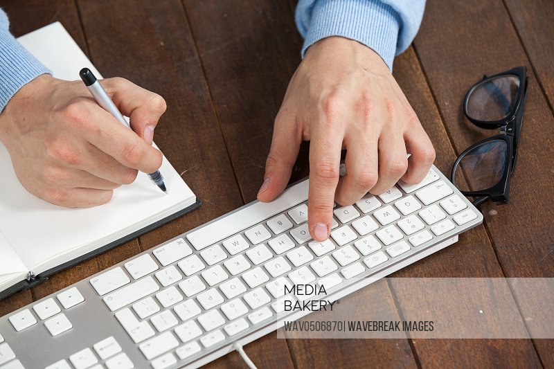 Man typing on keyboard and writing in diary on wooden table