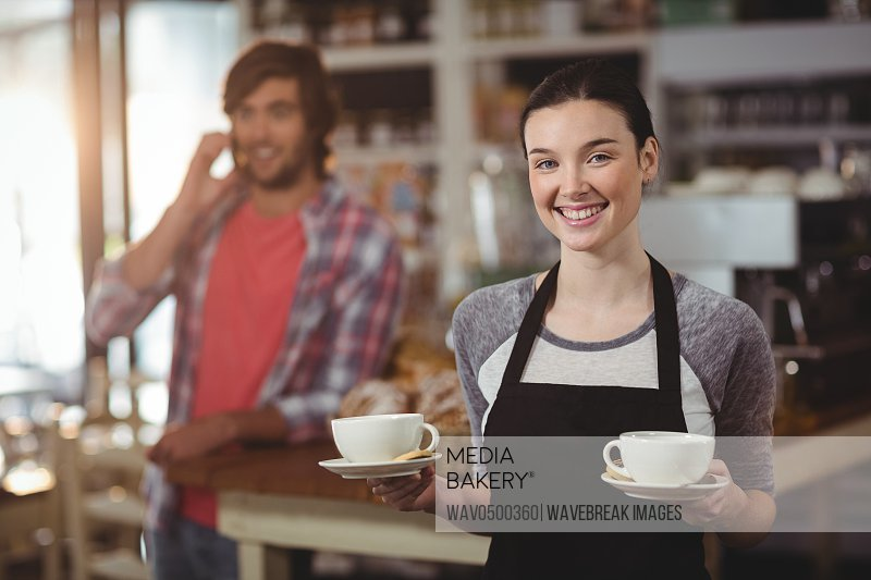 Portrait of waitress holding coffee cups in cafe