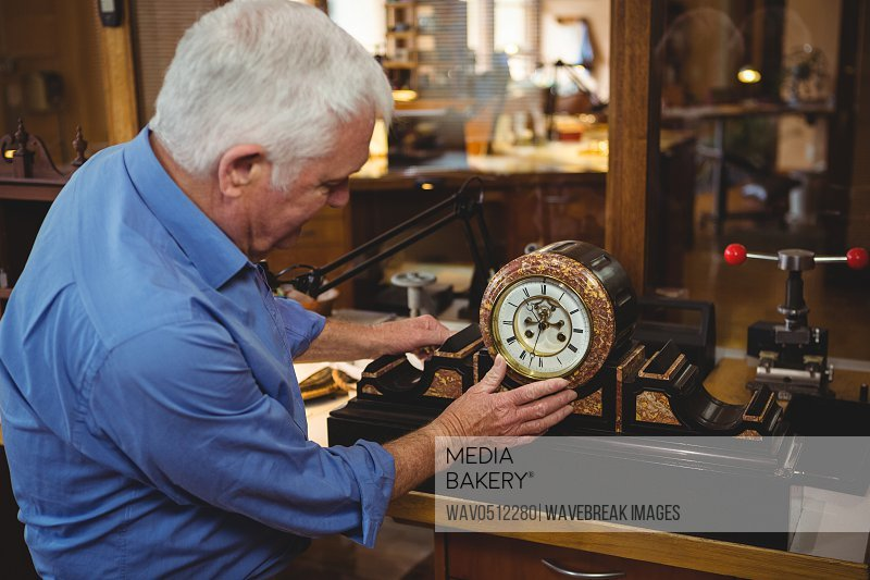 Attentive horologist checking a clock in workshop