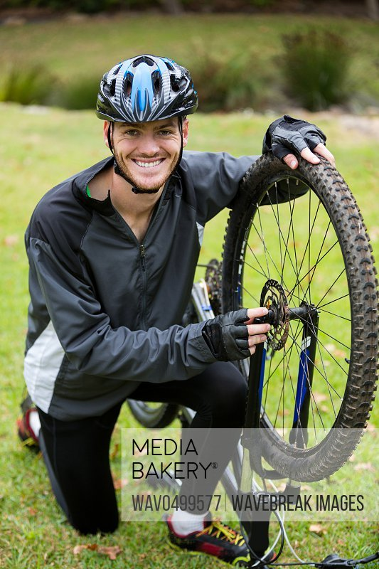 Portrait of smiling male cyclist repairing his mountain bike in park