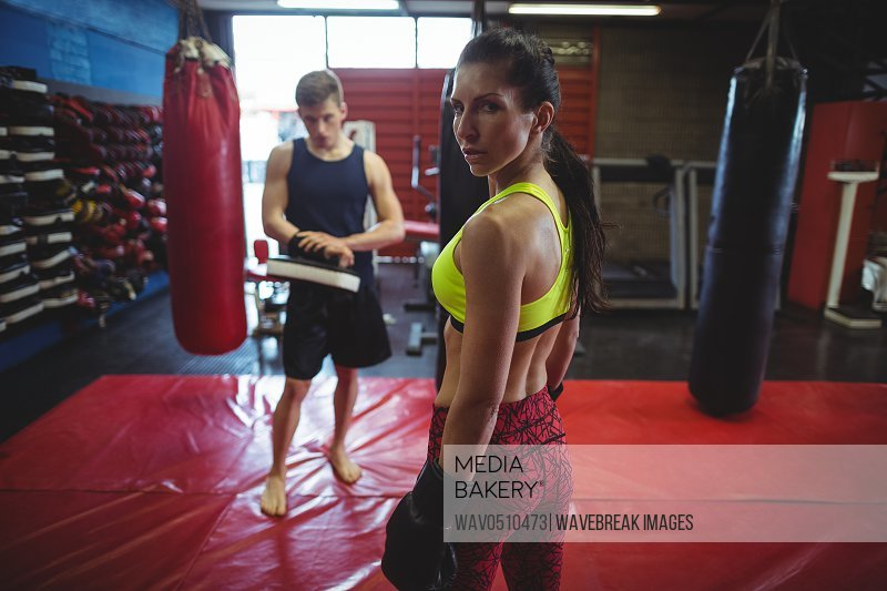 Female and male boxer standing in fitness studio during practice
