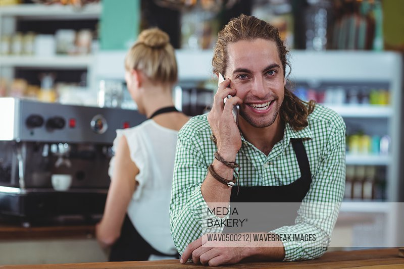 Portrait of waiter talking on mobile phone in cafe