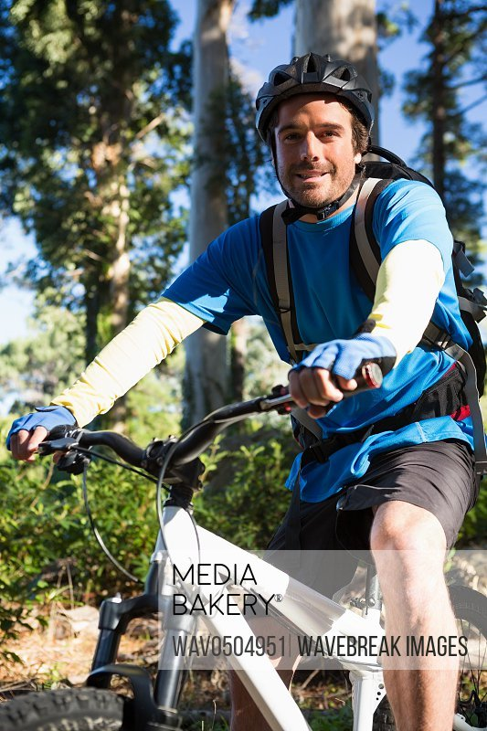 Portrait of male mountain biker with bike in the forest on a sunny day