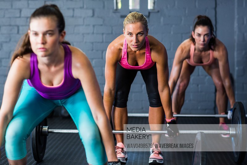 Portrait of female athletes lifting barbells in gym