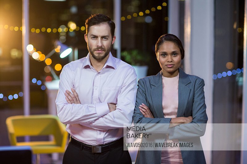 Businessman and woman standing with arms crossed in office at night