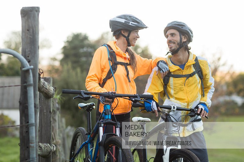 Biker couple interacting while standing with mountain bike in countryside
