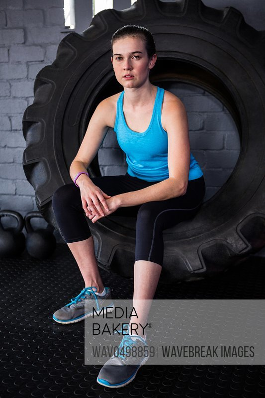 Portrait of serious female athlete sitting on tire in gym