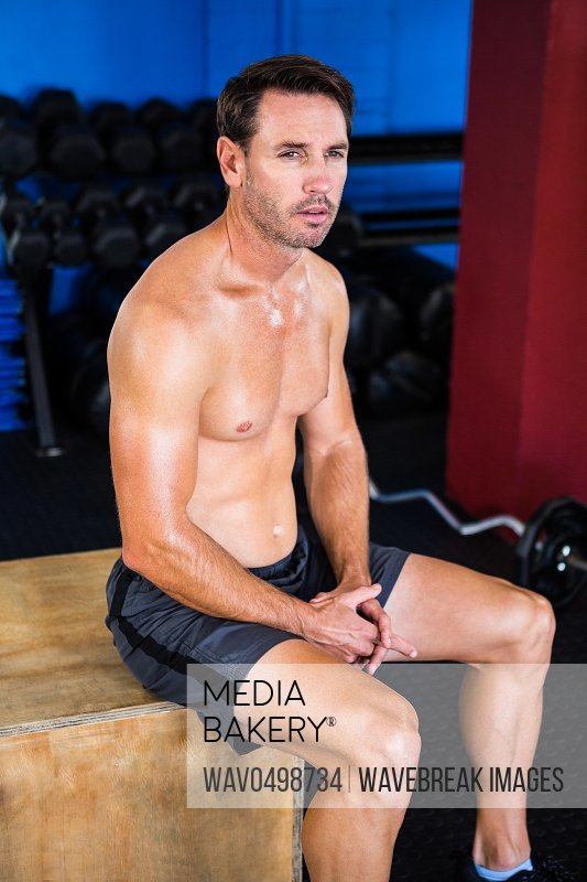 Thoughtful athlete sitting on cube in gym