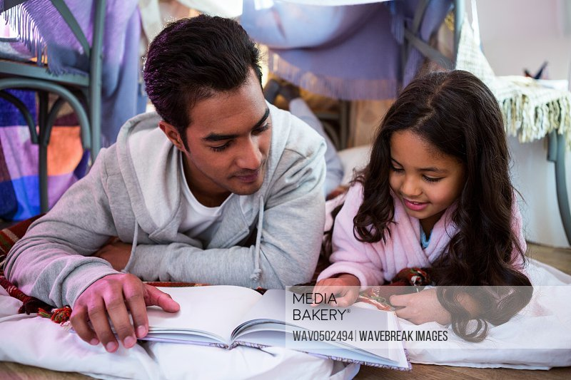 Father and daughter reading book at home