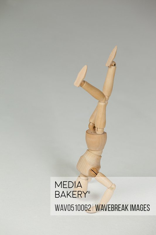 Wooden figurine performing a head stand against white background