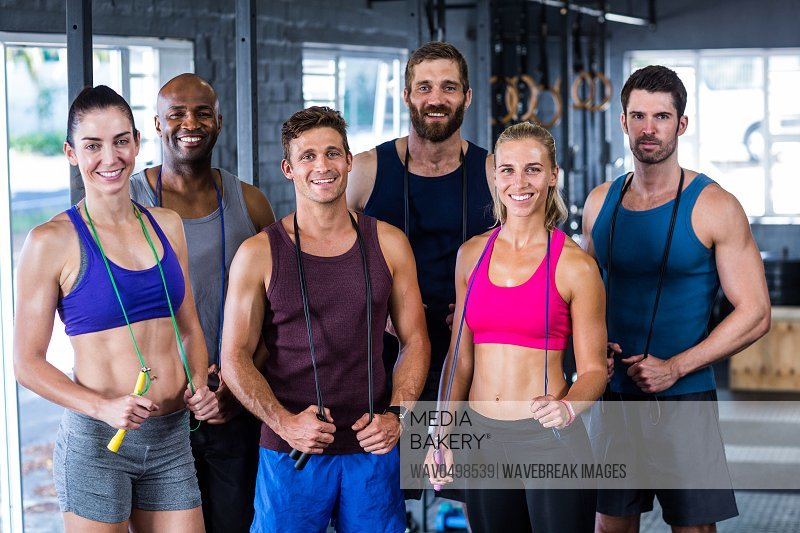Portrait of smiling friends with jumping ropes while standing in gym