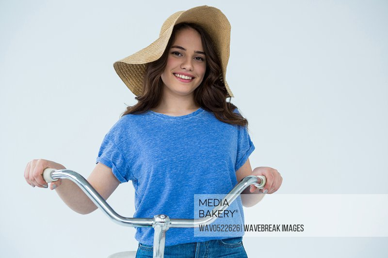 Beautiful woman in blue top and hat holding bicycle