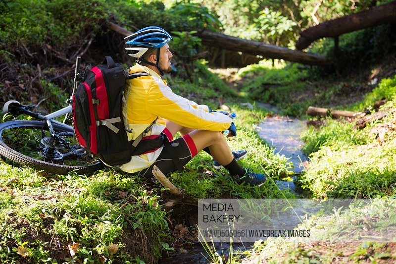 Mountain biker sitting near a stream and looking at nature in the forest