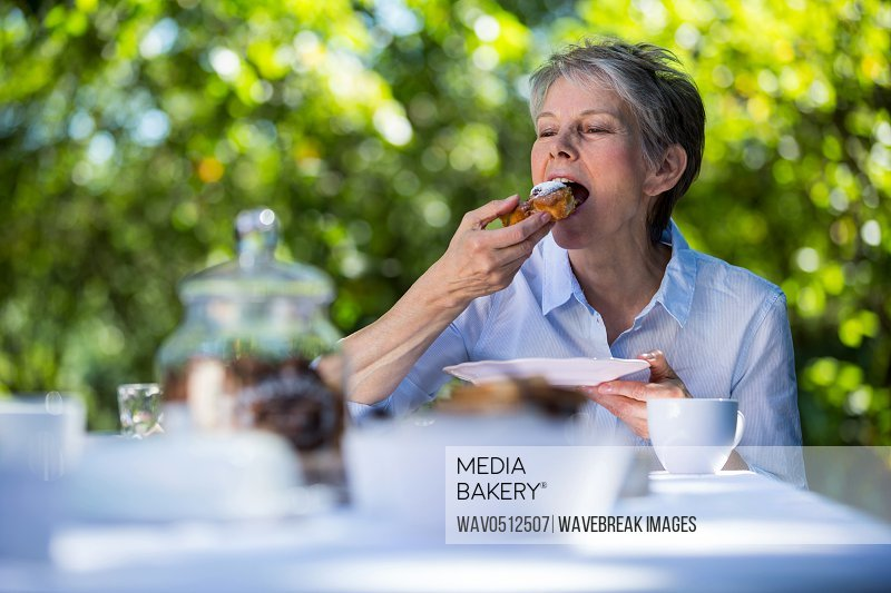 Senior woman eating sweet food in garden on a sunny day