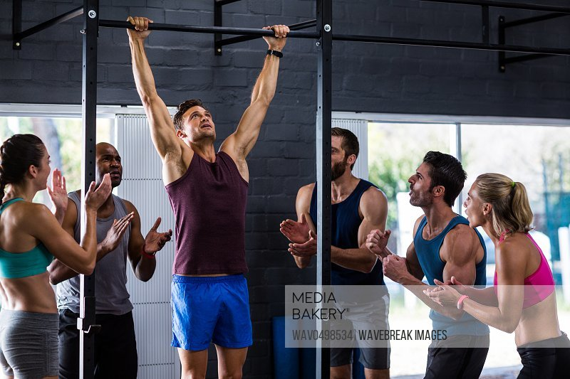 Friends cheering man doing chin-ups in gym