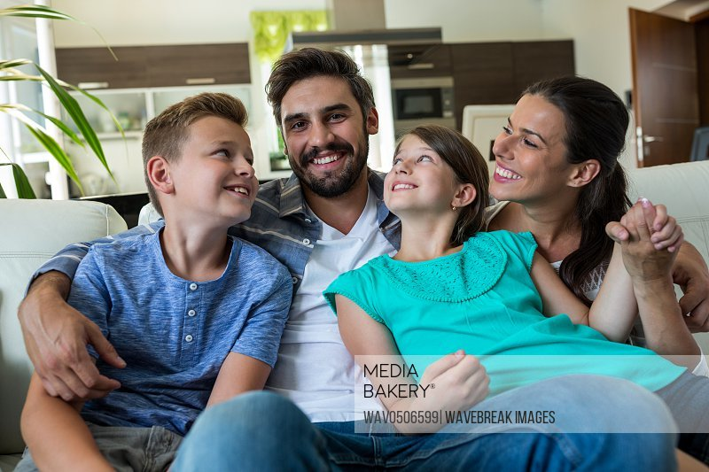 Happy family sitting with arm around on sofa at home