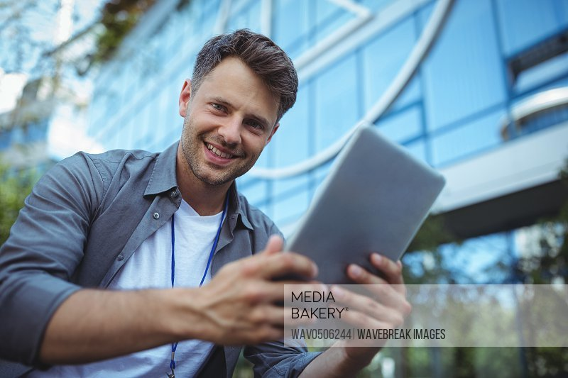 Portrait of business executive using digital tablet outside office