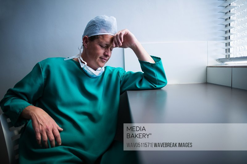Tensed male surgeon sitting at window in hospital