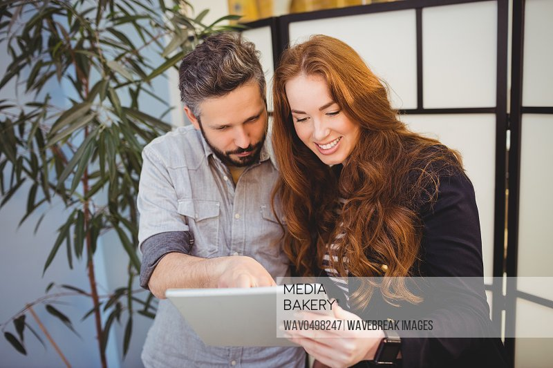Happy businesswoman with colleague using digital tablet in creative office