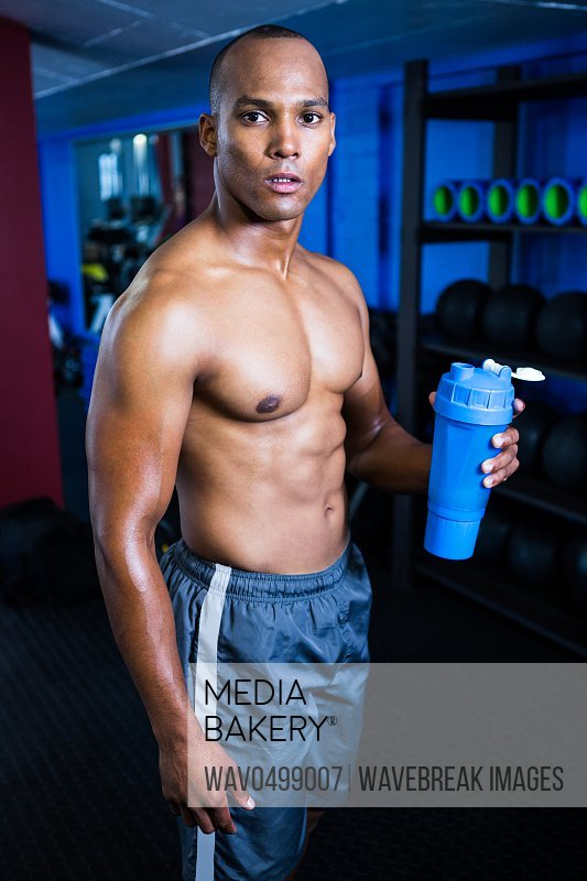Portrait of muscular shirtless man holding bottle in gym